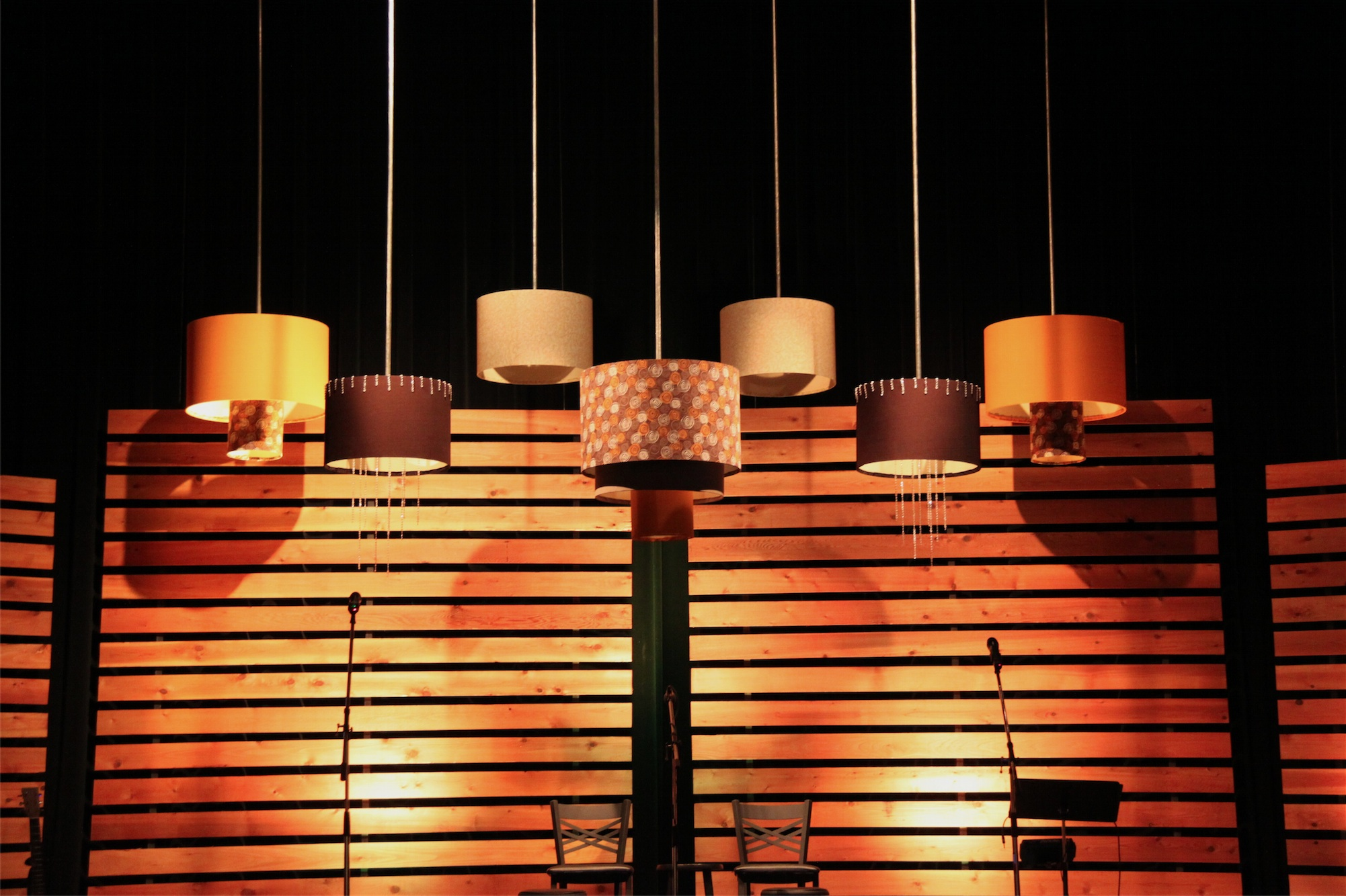 stage design with hanging paper lanterns and a fabric/wood grid